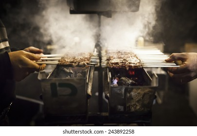 Barbecue with Arrosticini, a typical italian small skewers. A man on the right and another one on the left are taking a piece of meat