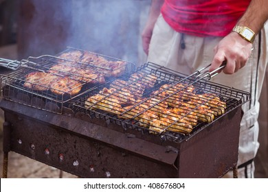 Barbecue. B-B-Q. Grille chicken meat on the grill. Summer rest. A man preparing chicken meat on the grill