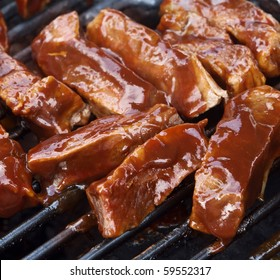 barbecue beef spare ribs cooking on a grill outdoors in summer