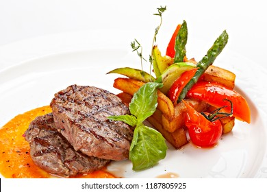 Barbecue Beef Steaks medium rare with grilled potaoes and vegetables.