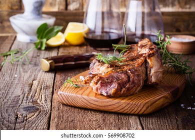 Barbecue bone ribeye steak on rustic cutting board ready to eat, delicious dinner with glass of wine