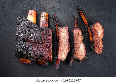 Barbecue burnt chuck beef ribs marinated and sliced with hot chili sauce as top view on an old rustic metal sheet