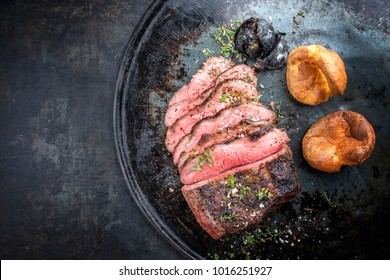 Barbecue caveman wagyu roast beef sliced with Yorkshire pudding as top view on a tray with copy space left