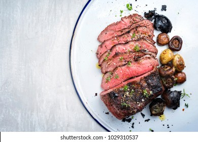 Barbecue caveman wagyu roast beef sliced with mushrooms and potatoes as top view on a tray with copy space left