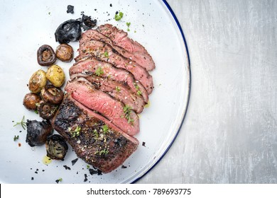 Barbecue caveman wagyu roast beef sliced with mushrooms and potatoes as top view on a tray with copy space right