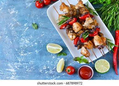 Barbecue of chicken on skewers with vegetables on a blue concrete background. Picnic.