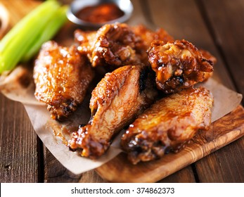 barbecue chicken wings close up on wooden tray shot with selective focus