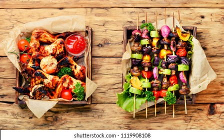 Barbecue chicken wings on wooden tray and grilled vegetables.BBQ.American food.BBQ chicken wings