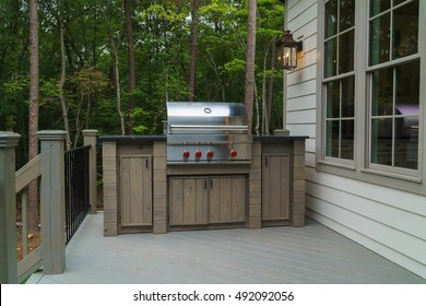 Barbecue cooker on  deck with  trees in background