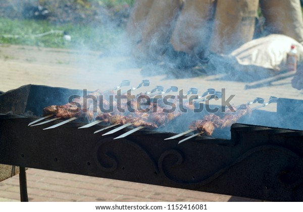 barbecue cooking meat on skewers on the coals