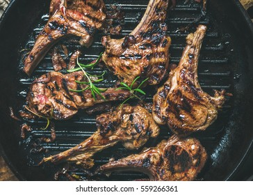 Barbecue dinner. Grilled lamb meat chops with onion and rosemary in black cast iron pan, top view, close-up. Slow food concept