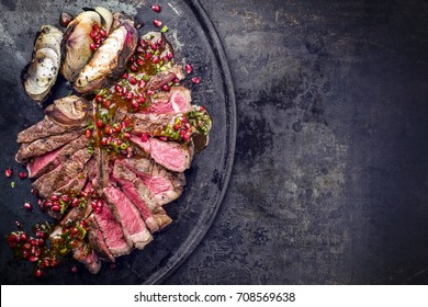 Barbecue dry aged caveman wagyu porterhouse steak with onion and pomegranate salsa as top view on a board with copy space on right