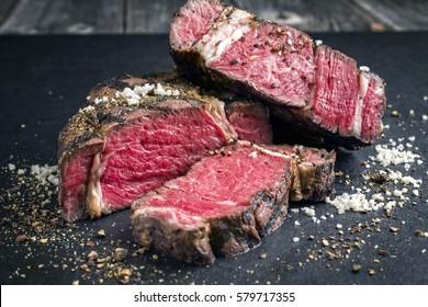 Barbecue dry aged Kobe Rib Eye Steak as close-up on a black slate