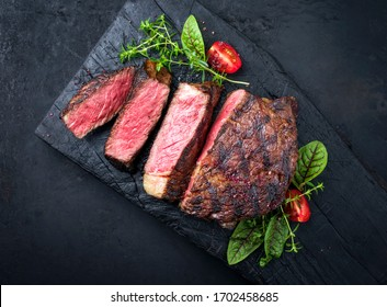 Barbecue dry aged wagyu entrecote beef steak with lettuce and tomatoes as top view on an old charred wooden board with copy space