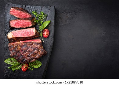 Barbecue dry aged wagyu entrecote beef steak with lettuce and tomatoes as top view on an old charred wooden board with copy space right