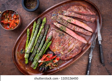 Barbecue dry aged wagyu flank steak with green asparagus and chili relish as top view on a plate