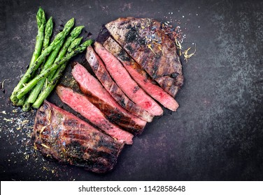 Barbecue dry aged wagyu flank steak sliced with green asparagus as top view on an old rusty board with copy space right