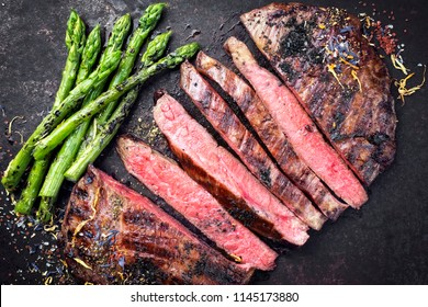Barbecue dry aged wagyu flank steak sliced with green asparagus as top view on an old rusty board
