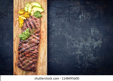 Barbecue dry aged wagyu flank steak with corn, avocado and chimichurri sauce as top view on a cutting board
