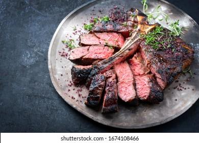Barbecue trockengealtes, gegrilltes Rinderhacksteak mit großem Filet Stück mit Kräutern und rotem Salz als Draufsicht auf einem modernen Design rustikalen Platte mit Kopienraum links