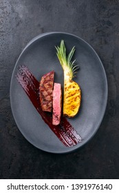Barbecue dry aged wagyu roast beef with grilled pineapple peace and hot smoked sauce as top view on a modern design plate with copy space