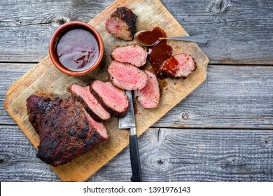 Barbecue dry aged wagyu tri tip steak with BBQ sauce as dip as top view on a wooden cutting board with copy space