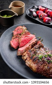 Barbecue dry aged wagyu tri tip steak sliced with hot sauce and tomato onion skewer as closeup on a modern design cast iron plate