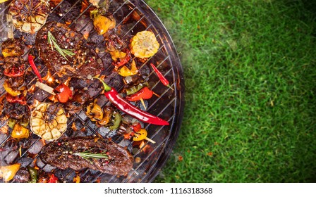 Barbecue garden grill with beef steaks on green grass, top view, close-up.