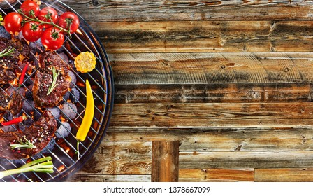 Barbecue garden grill with beef steaks on rustic wooden table, top view