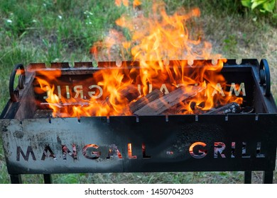 Barbecue grill with fire on nature background. Mangall-grill. Fire closeup.