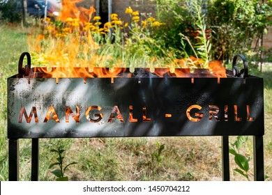 Barbecue grill with fire on nature background. Mangall-grill.