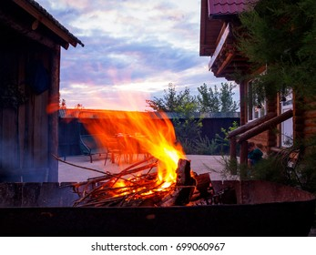 Barbecue grill with fire on nature, outdoor, close up. Hot empty BBQ charcoal grill with flames in the background of beautiful sunset. House territory. Cookout Concept.
