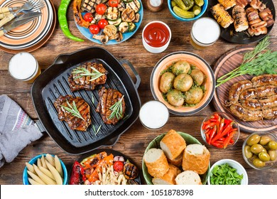 Barbecue, grill and food concept. Top view of fresh beef steaks, skewers and vegetable on grills placed on wooden background. Barbecue, grill and food concept