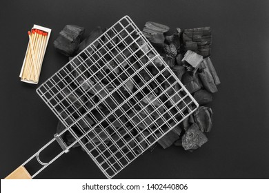 Barbecue grill grid on charcoal pieces and a box of matches. BBQ preparation set. Black background. Flat lay.