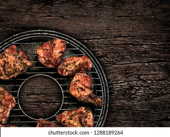 barbecue grill with meat and spices on a wooden table