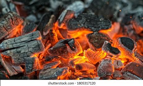 Grillgrube mit glühenden und brennenden Kohlebriketts, Nahaufnahme