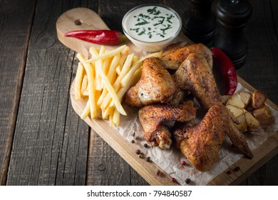 Barbecue grilled chicken wings close up with fries, tomato ketchup sauce and beer on wooden background. Meat food concept.