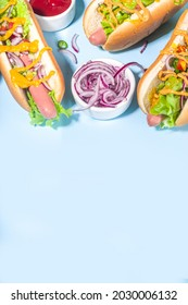 Barbecue grilled fastfood, Various traditional american hot dogs set with sausage, yellow mustard, ketchup and fresh vegetables salad, top view on bright blue background with french fries