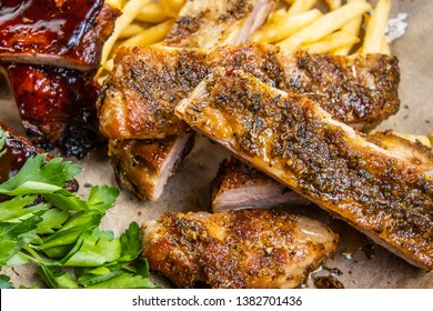 barbecue grilled pork ribs on parchment with French fries and hot pepper.