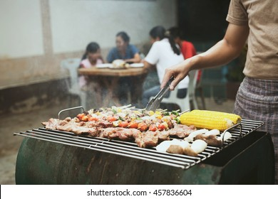Barbecue grills in relax time of family party, asian men's cooking meat, corn, mushroom and barbecue grill for his family people.