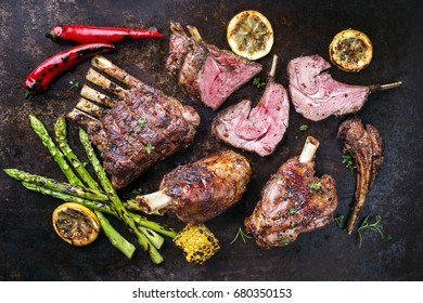 Barbecue Leg of Lamb and Veal Loin with Vegetable as top view on old metal sheet