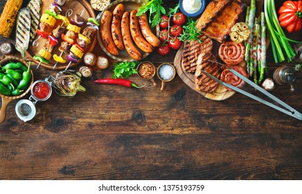 Barbecue menu. Grilled meat and vegetables on rustic wooden table with copy space for text