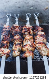 Barbecue on the grill. Shashlik made of cubes of meat on the skewers during of cooking on the mangal over charcoal outdoors