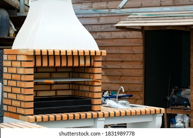 Barbecue open fireplace for cookout food. Outdoor BBQ Grill. Open Summer Kitchen. Barbeque Grill Made From Bricks On The Backyard