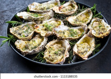 Barbecue overbaked fresh opened oyster with garlic and herbs offered as closeup on a tray