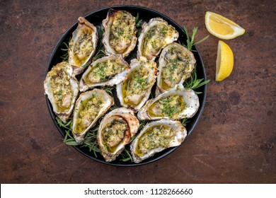Barbecue overbaked fresh opened oyster with garlic, lemon and herbs offered as top view on a tray