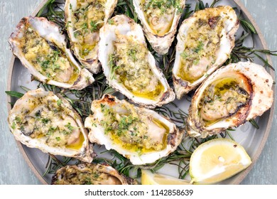 Barbecue overbaked fresh opened oyster with garlic, lemon and herbs offered as top view on a plate