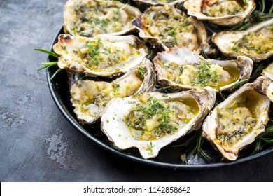 Barbecue overbaked fresh opened oyster with garlic and herbs offered as top view on a plate