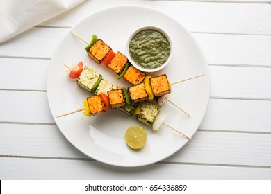 barbecue Paneer Tikka Kabab - Indian Tandoori cottage cheese cubes in red and white sauce in sticks, served in a plate with green chutney over colourful or wooden table top,selective focus