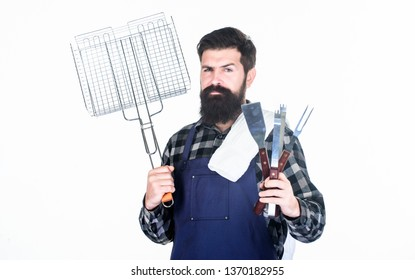 Barbecue party. Grill cook using portable barbecue cooking tools. Happy hipster holding stainless steel tools for preparing barbecue food. Bearded man with barbecue grid and utensils in hands.